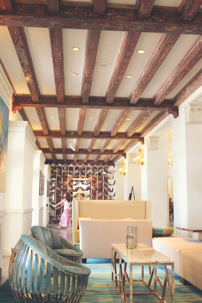 Original hand-stenciled pecky cypress ceiling beams above one of many cozy nooks in the Vinoy's grand lobby