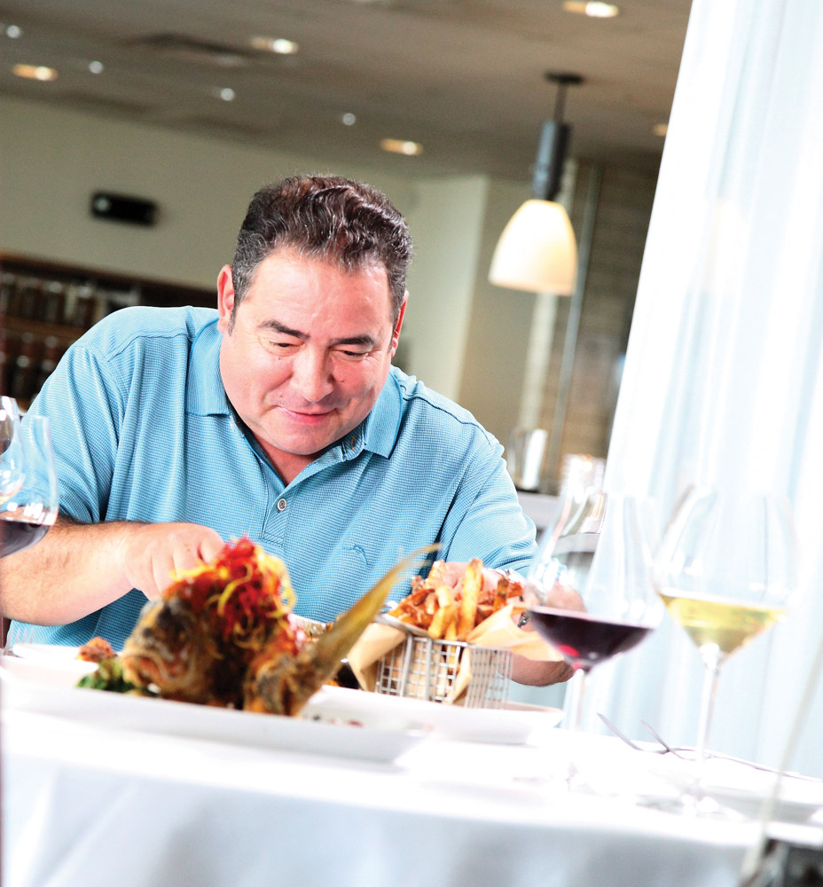 Emeril Lagasse cuts into crispy-fried snampper at V Seagrove restaurant, one of Chef David Cunningham's signature dishes. VIE Magazines in depth look at Emeril and Alden Lagasse, A Bountiful Life.