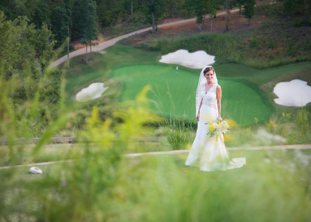 Bride standing on golf green at Vaughn and Tim Spanjer wedding Hamilton Place at Pursell Farms