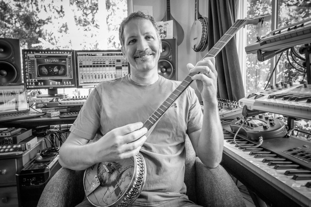 Composer James Kernick playing banjo in recording studio