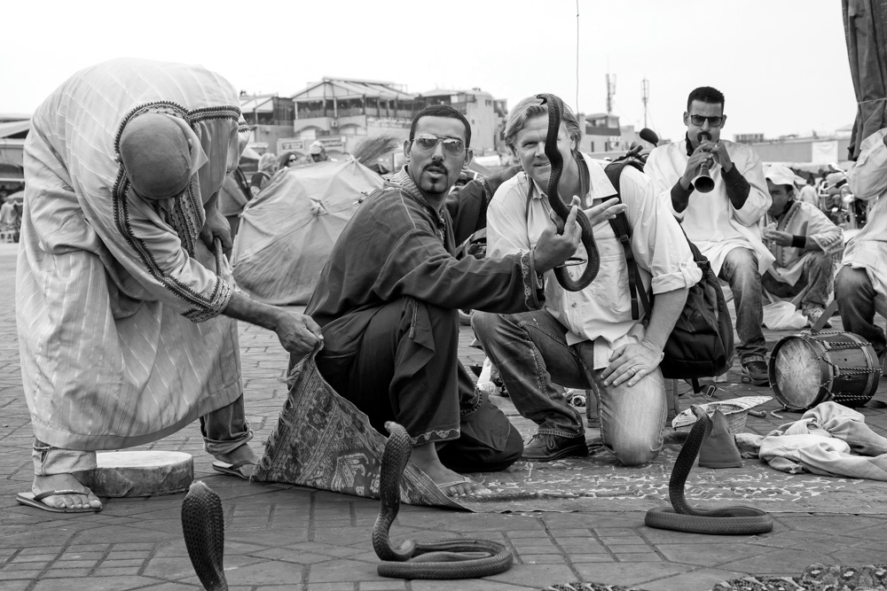 Street performer placing deadly snakes on tourist head in Morocco