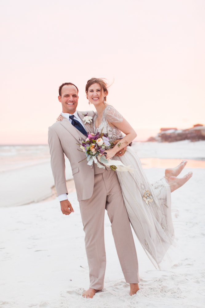 Wedding Event Specialists groom holding up bride while posing on the beach. Photo by Mad Love Weddings