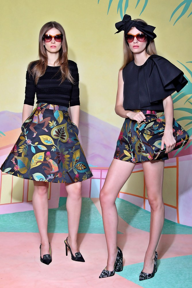 two models wearing black dresses designed by christian siriano