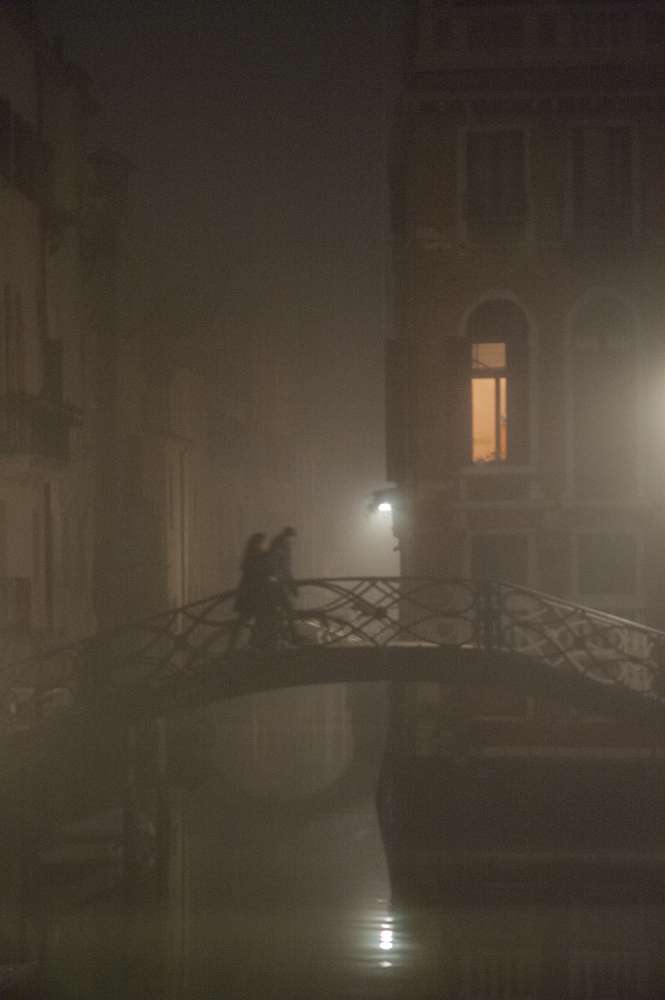Couple walking over bridge in Venice, Italy.