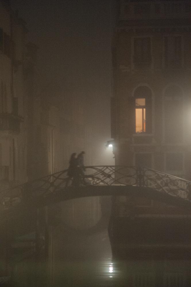 Couple walking over bridge in Venice, Italy.