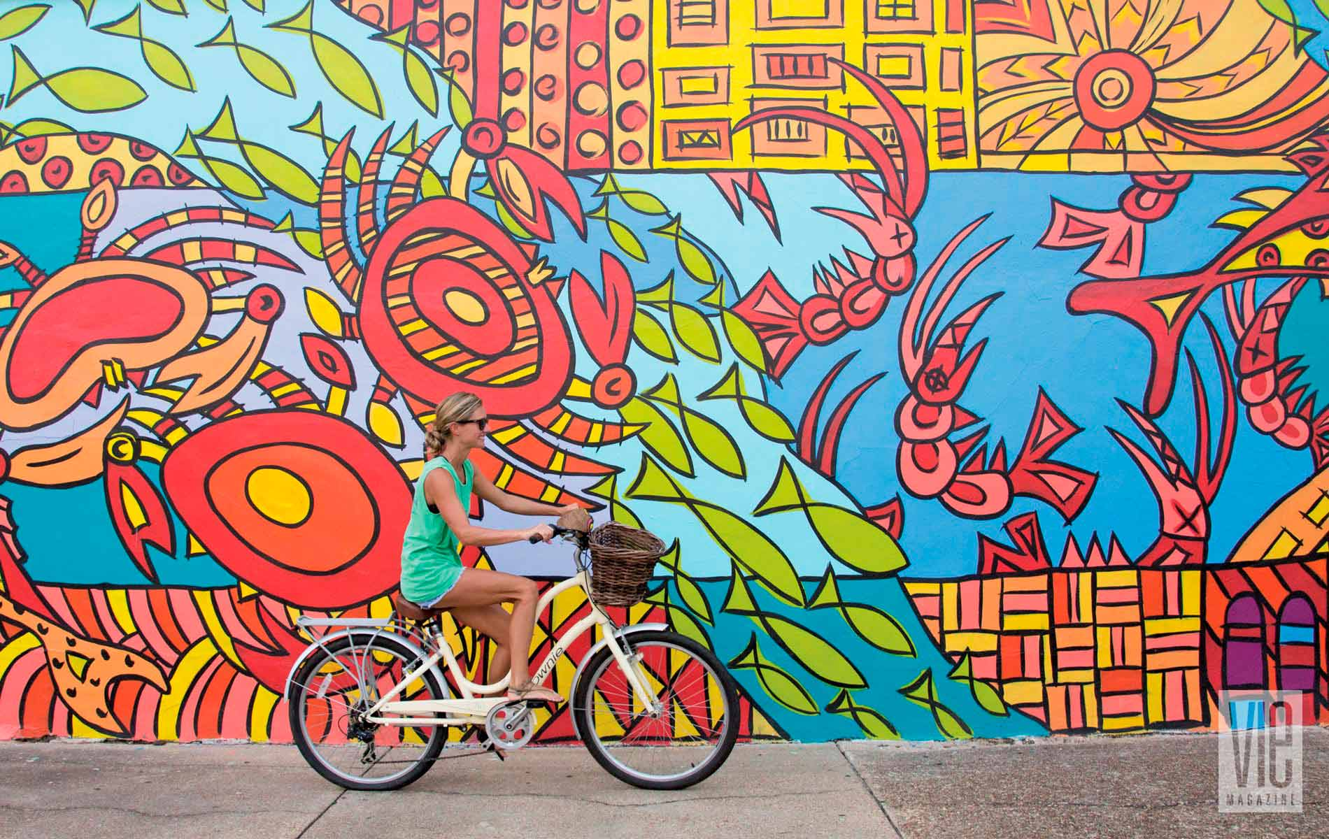 Chelsey Allegri rides her bike downtown past Aboriginal Sealife, a mural painted by Ameri'ca Jones.