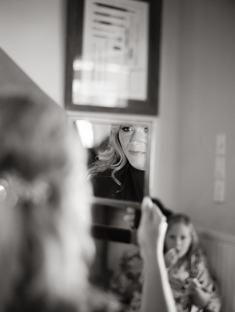 Bride, Jennifer Goff, checking her makeup in the mirror