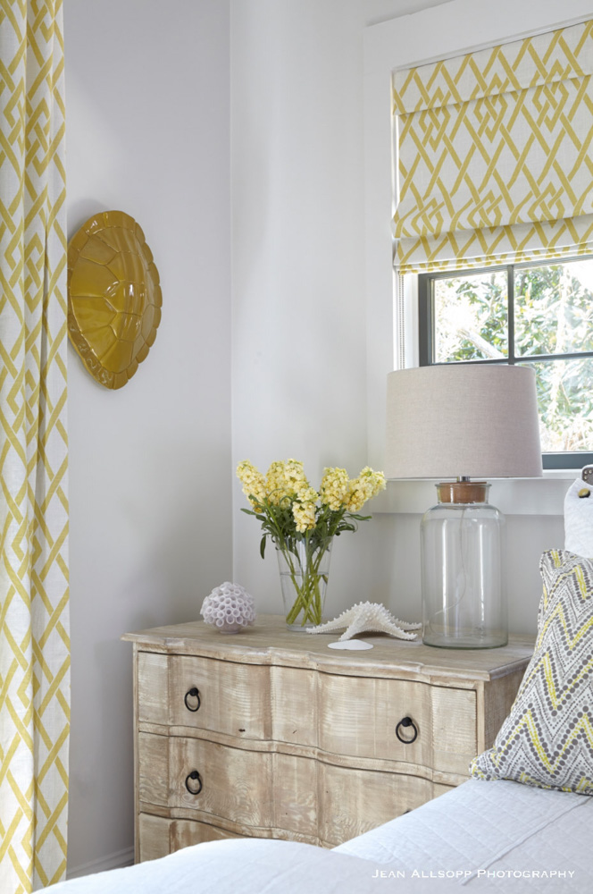 Bedside table with yellow flowers and curtains