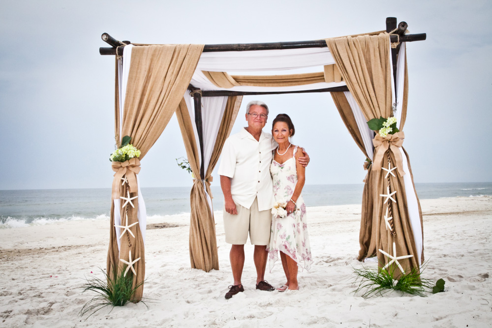 Husband and wife stand under beach alter