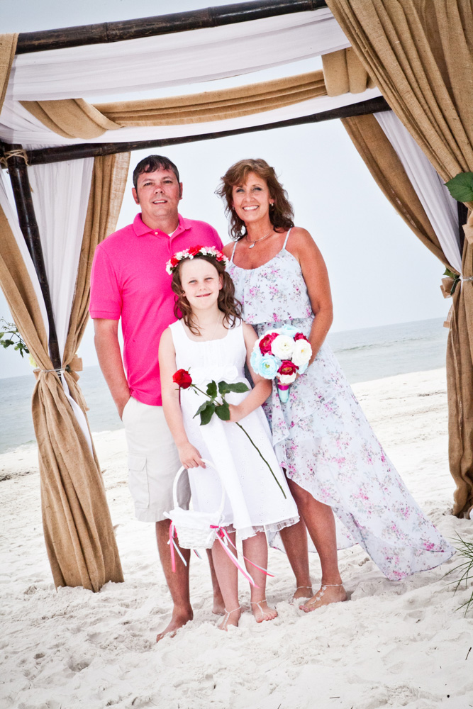 Family stand under beach alter