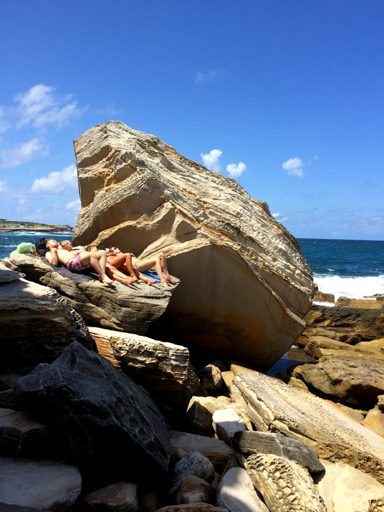 Sunbathing on the rocks at the Coogee Beach bogey hole, Sydney, Australia