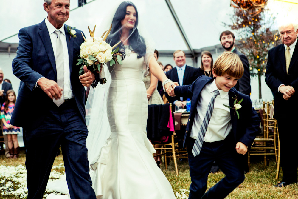 Little boy holds bride's hand with father down aisle