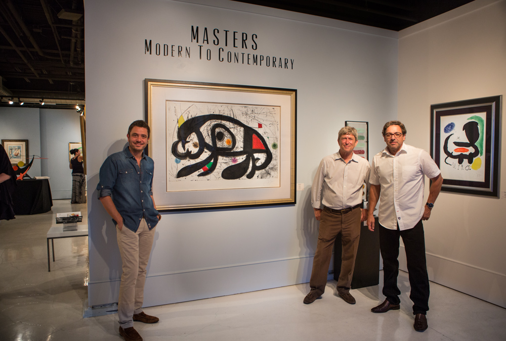Three men posing with paintings in art gallery