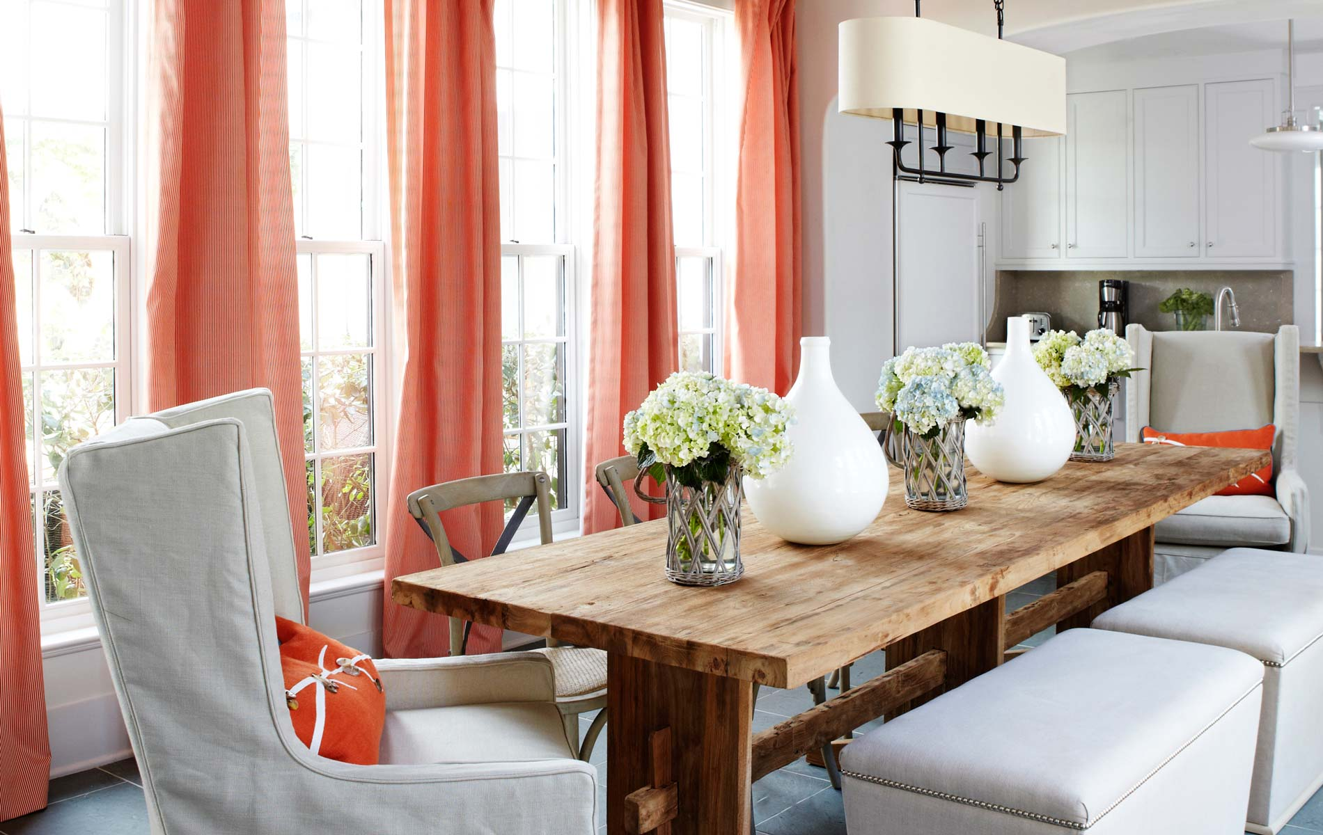 Wood table with coral curtains and white chairs