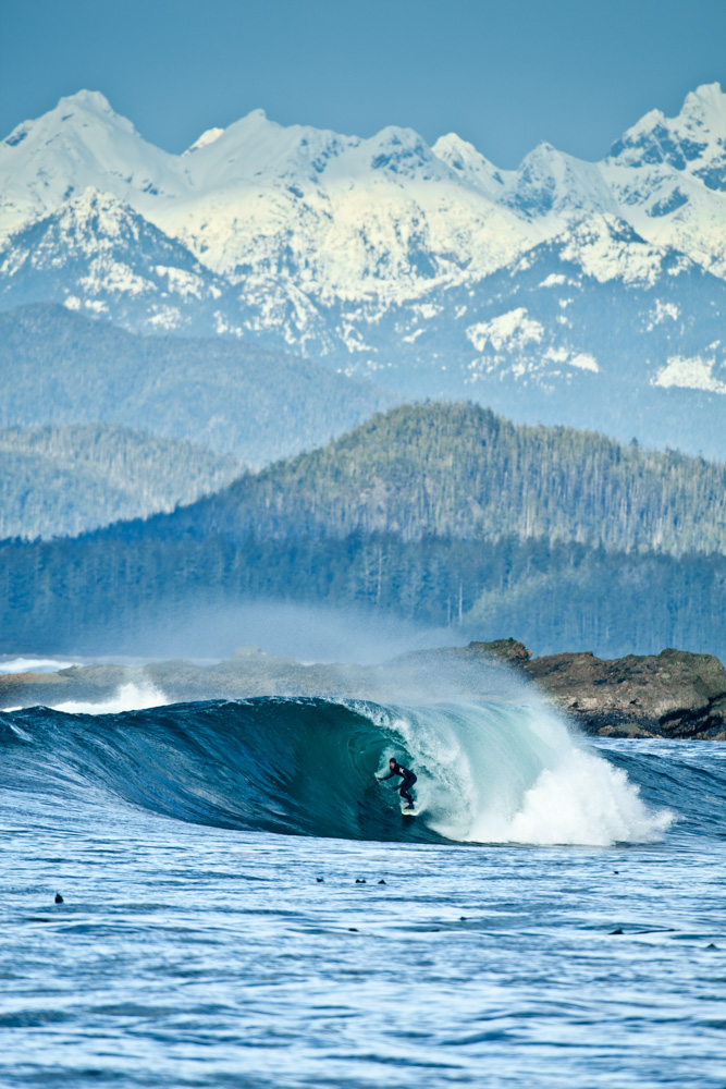 Surfer riding curled wave with greenery and snowy mountains in the background at Vancouver Island, Canada