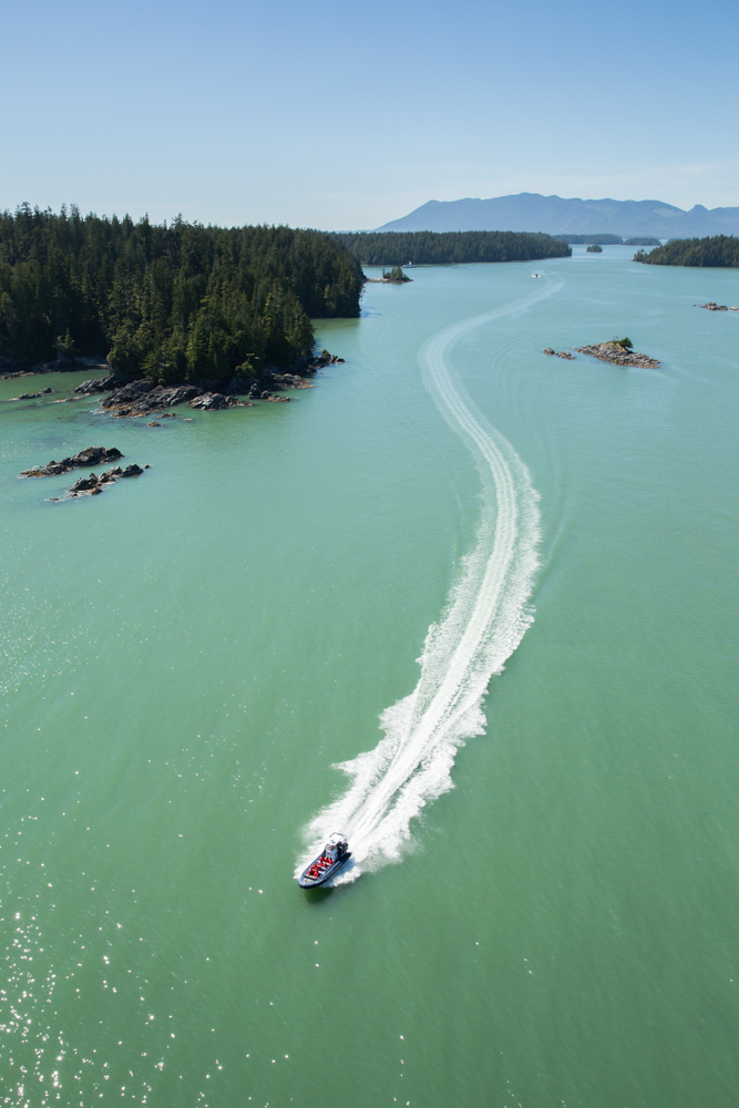Aerial view of a boat jetting across blue green waters near Vancouver Island, Canada