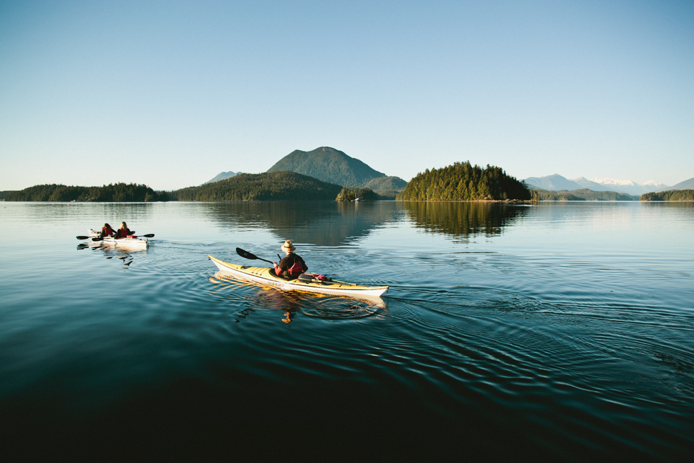 Vacationers kayaking with mountains in the distance in Vancouver Island, Canada