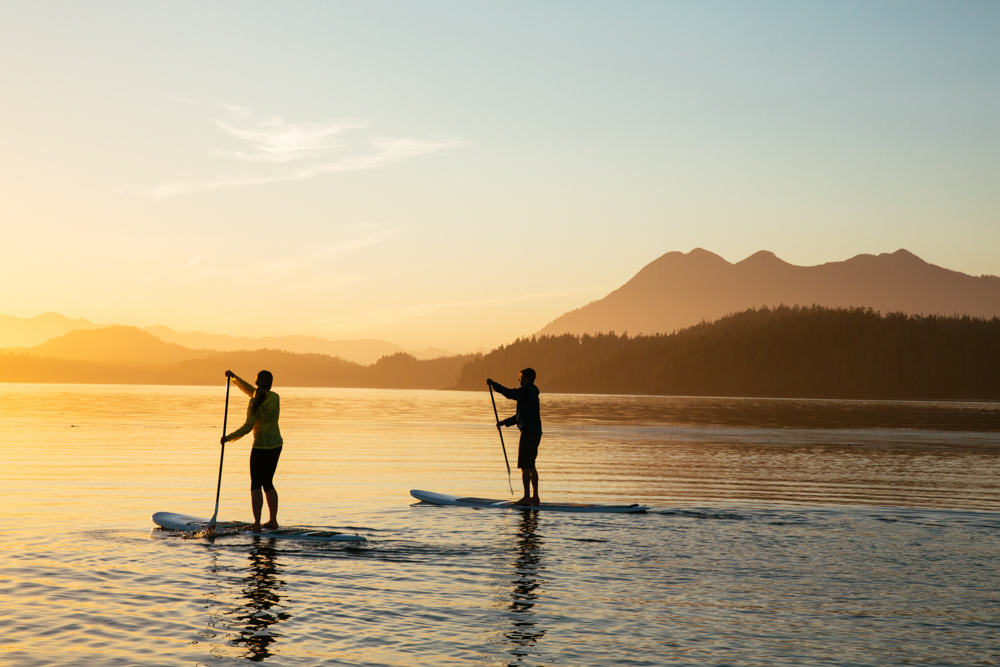 Two people paddleboarding on the water with mountains sitting in the background in Vancouver Island, Canada