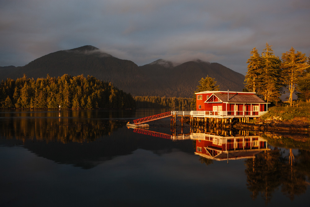 Red lake house sitting on edge of water with mountains in the distance in Vancouver Island, Canada