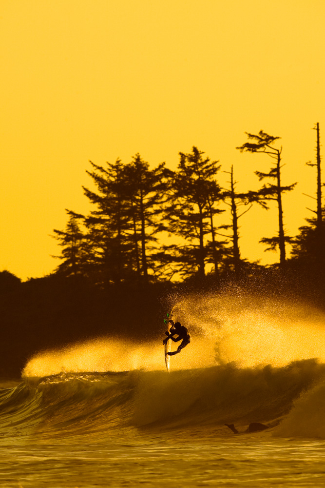 Surfer catching air off of a wave at sunset at Vancouver Island, Canada