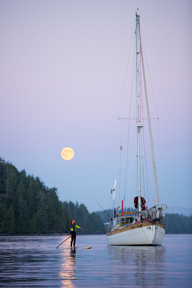 Man paddle boarding next to sailboat at twilight, with moon in the background at Vancouver Island, Canada