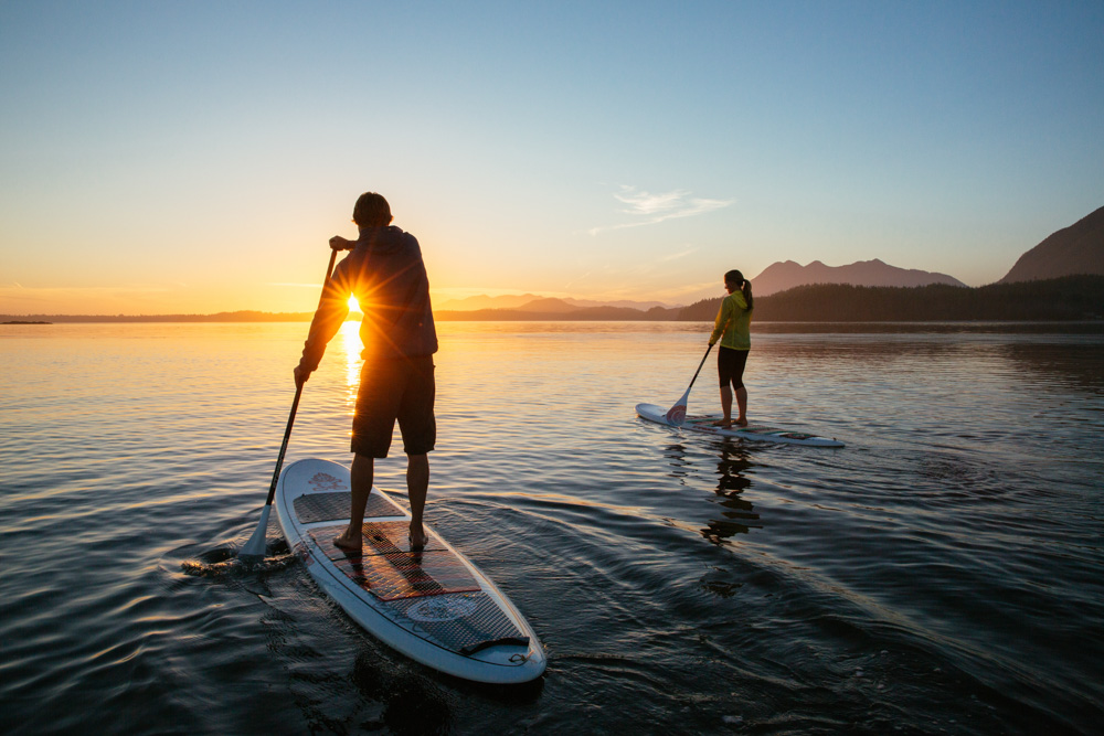 People paddleboarding at sunrise Vancouver Island, Canada