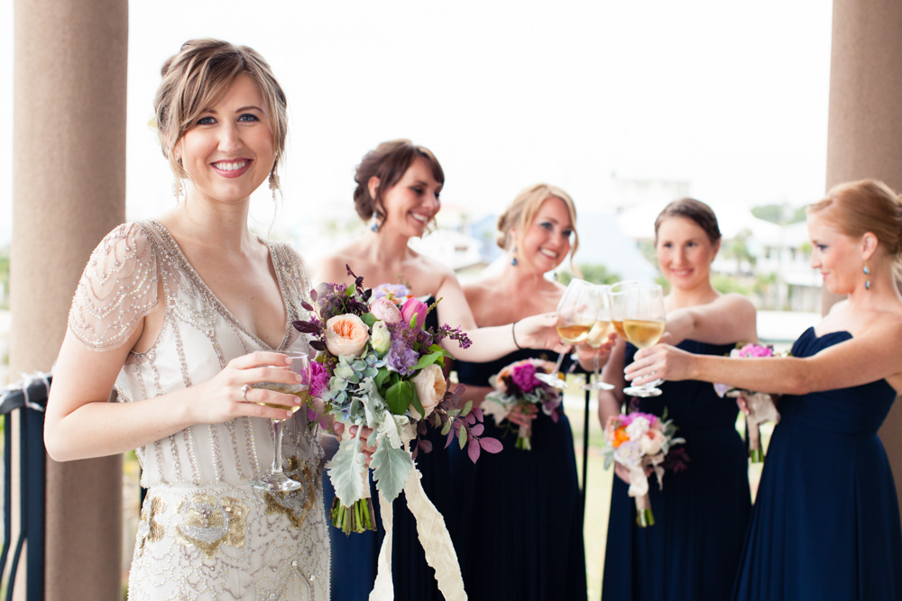 Wedding Event Specialists bride and bridesmaids toasting on the balcony. Photo by Mad Love Weddings