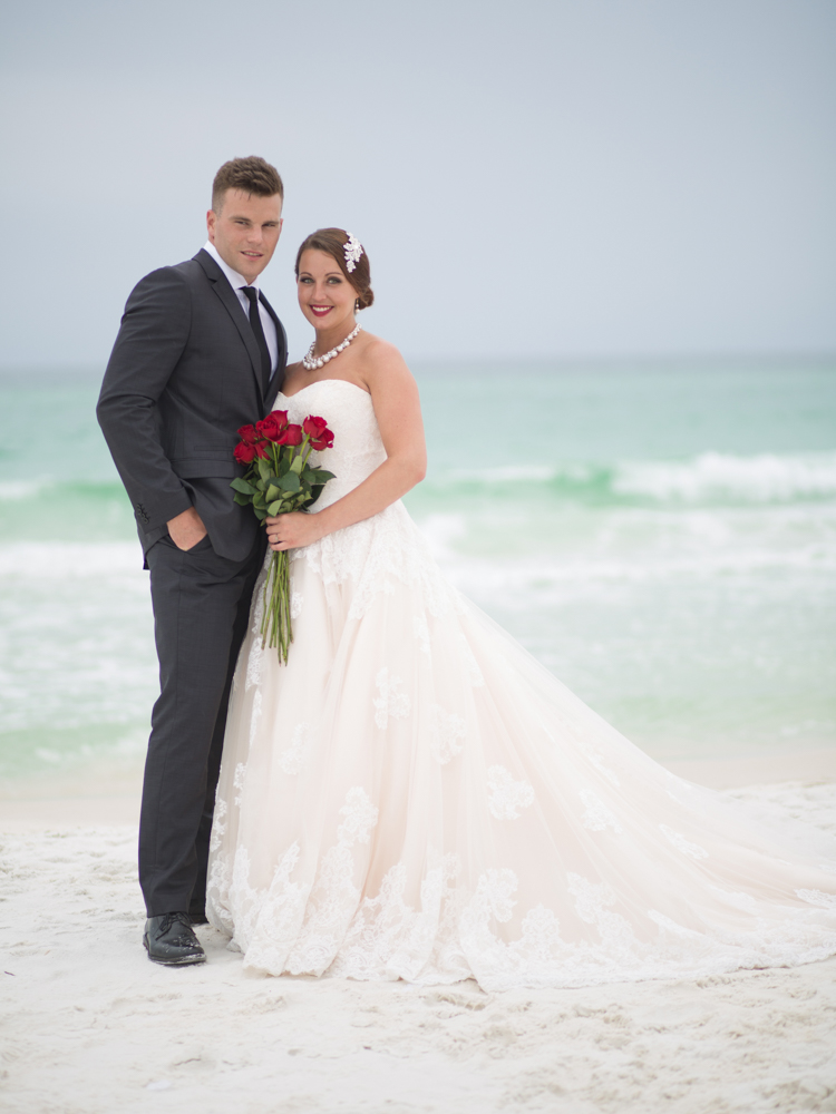 Wedding Event Specialists bride and groom posing on beach. Photo by Palafox Street Weddings