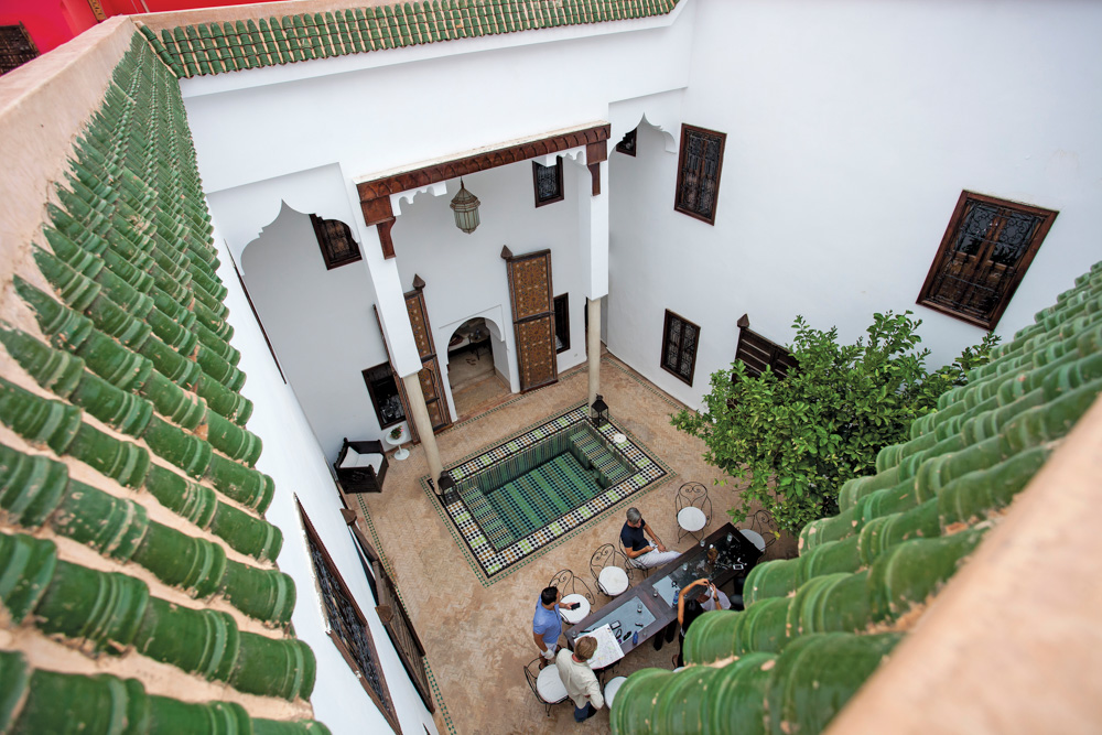 Open room with pool and people dining in Morocco