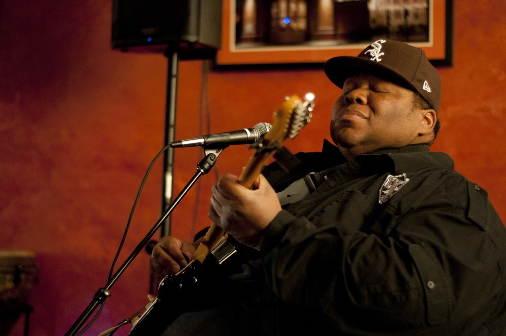 "Derwin ""Big D"" Perkins, guitarist, often closes his eyes while performing so as to connect with each musical note."