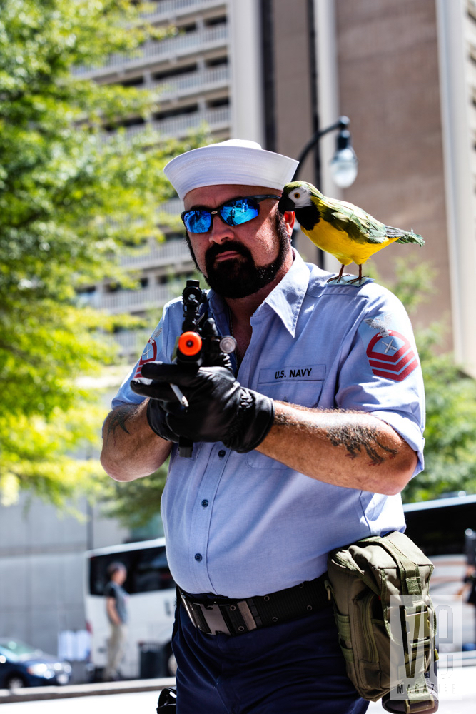 Guy holding a gun with a parrot costume dragon con