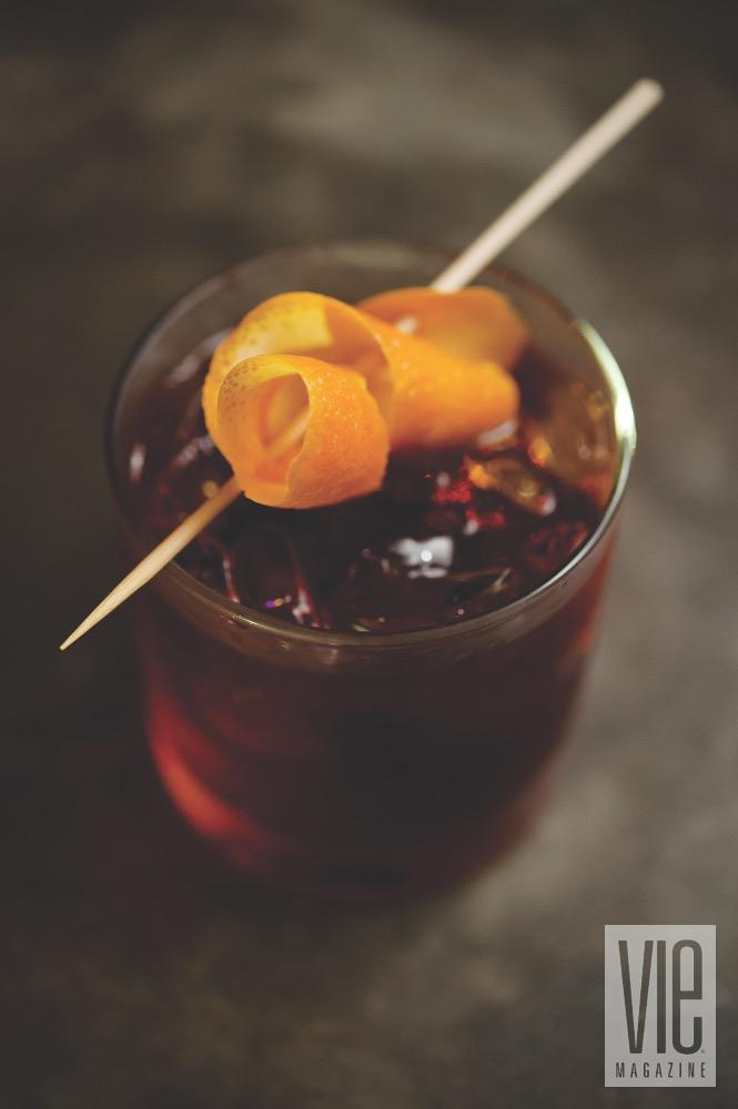 Borago's Chilled Red Cocktail With A Spiraled Orange Zest As A Garnish