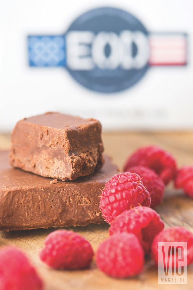 A Couple Bars Of EOD Chocolate Fudge With A Handful Of Raspberries