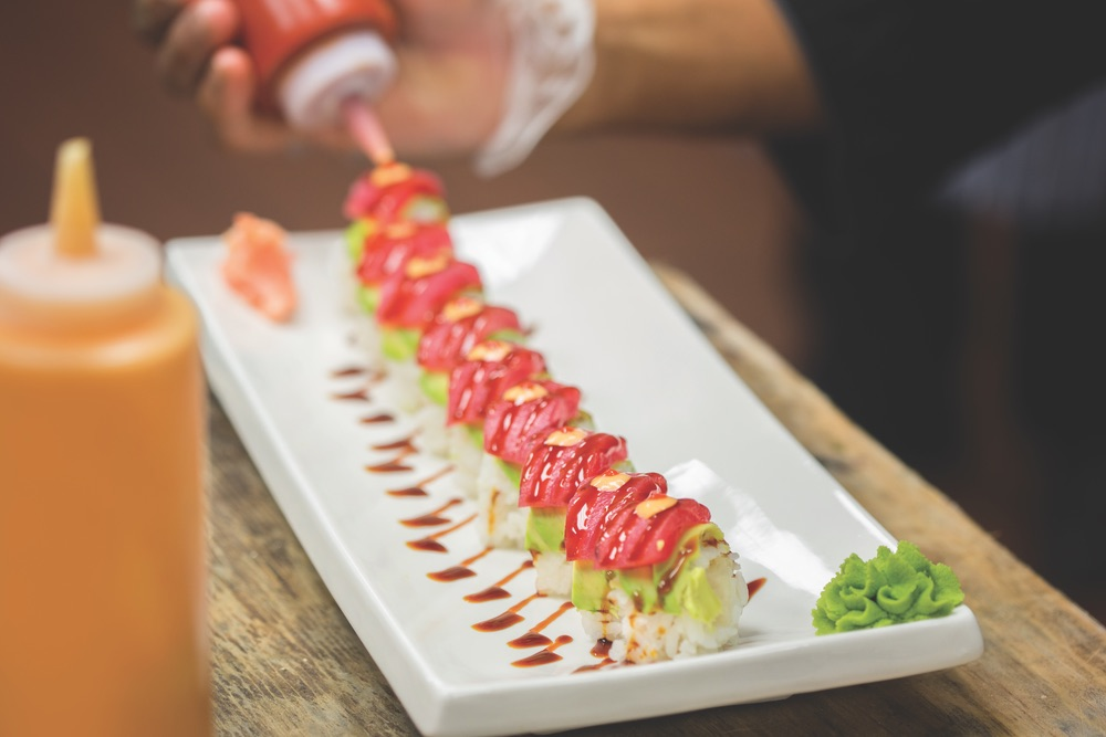 A Handmade Row of Salmon Topped Sushi with Drizzled Eel Sauce and Spicy Mayo