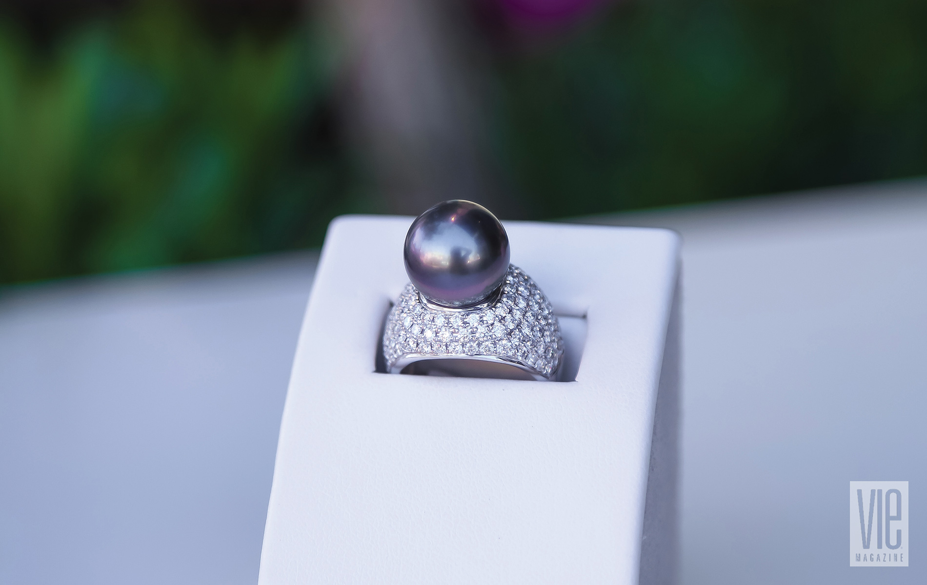 A Big Black Pearl Cocktail Ring Surrounded By A Setting Of Pave Diamonds Resting On A Ring Case