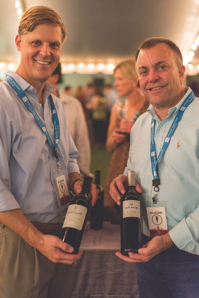 Two Friends Each Holding Up A Bottle Of Wine At The Seeing Red Wine Festival