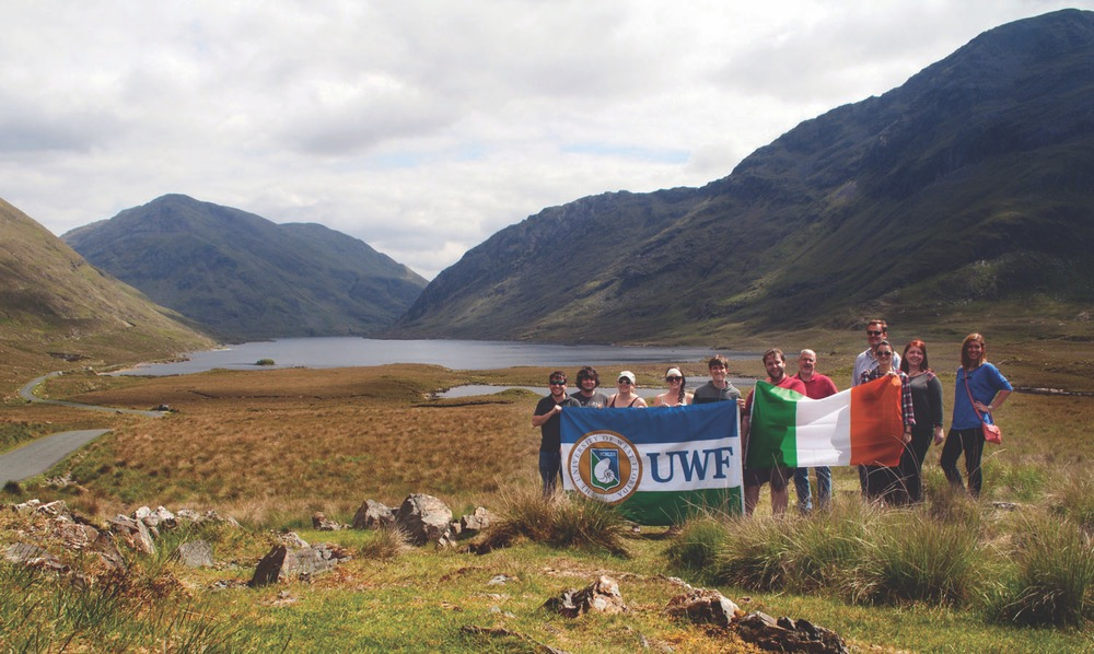 University of West Florida Irish Experience Program Standing With UWF And Irish Flag With A Backdrop of Mountains