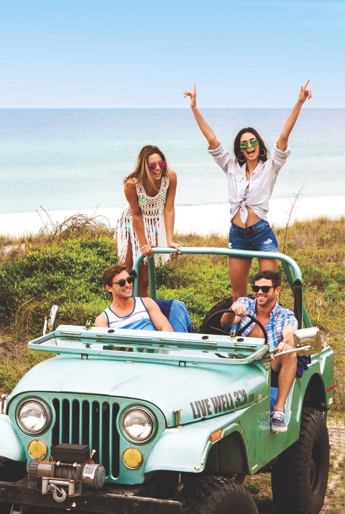 Young adults beach riding in a Jeep