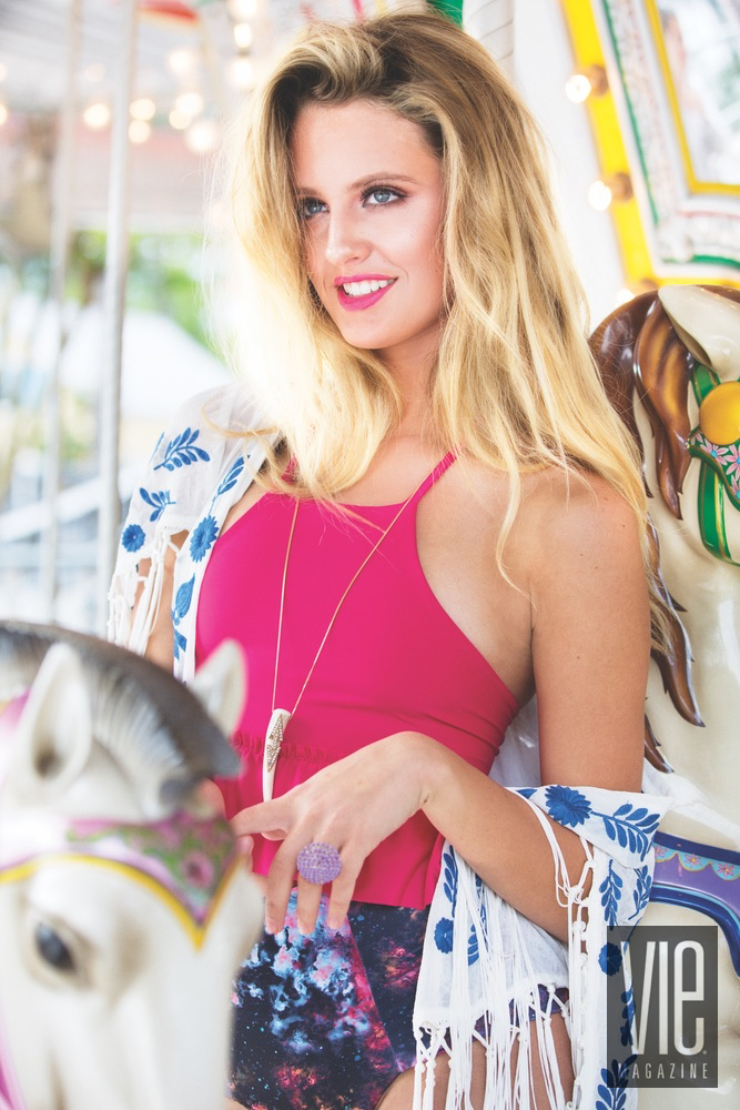 Emme Martin is a beautiful young model wearing a hot pink Cayce Collins swimsuit on a carousel in Baytowne Wharf
