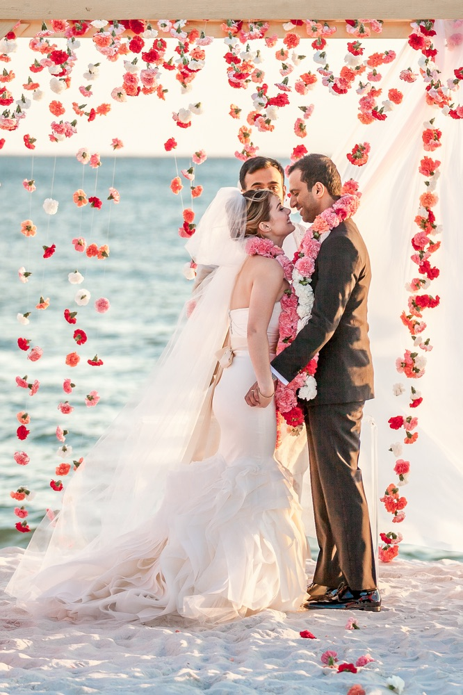 Married Couple With A Curtain Of Flowers On The Beach