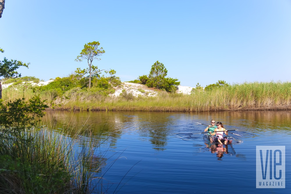 Couple canoeing in Klear Kanoos with sand dunes in the background
