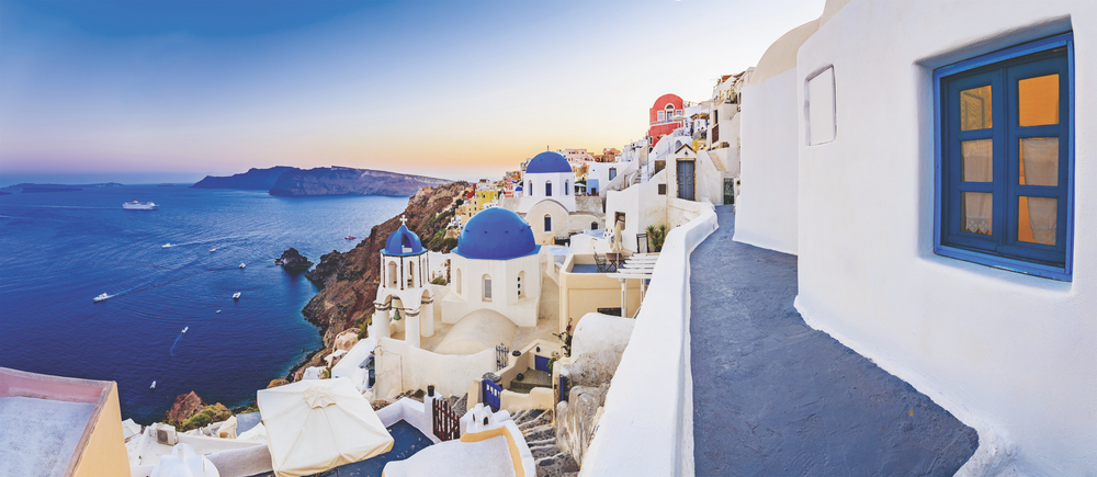 Santorini, Greece with the royal blue waters of the Aegean Sea swimming below Gem of the Aegean Oia sapphire rooftops