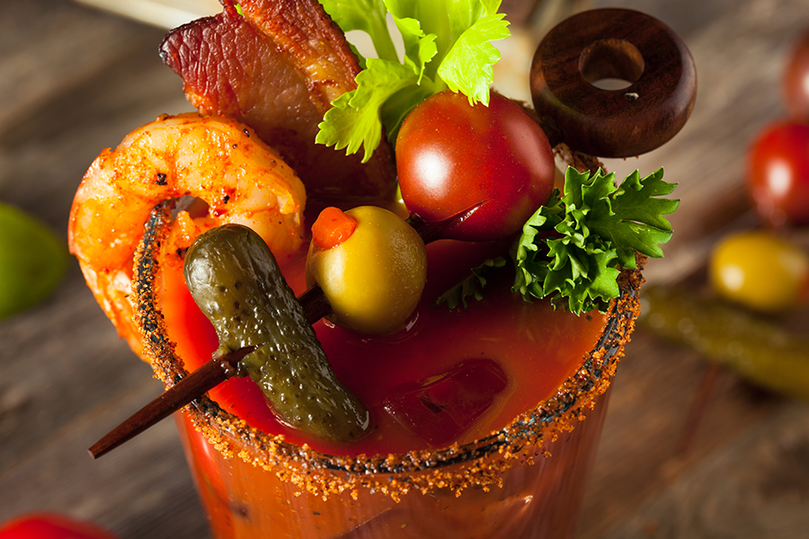 Bloody Mary garnished with shrimp cocktail bacon and olives