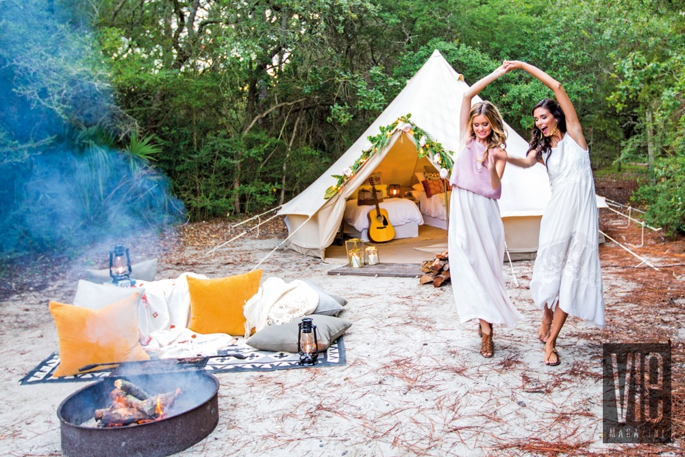 Models laughing and dancing outside of their Fancy Camps tent glamping