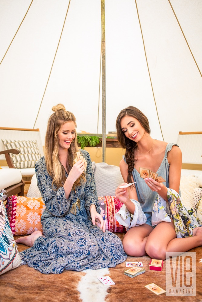 Models playing card games inside their Fancy Camps tent glamping VIE magazine