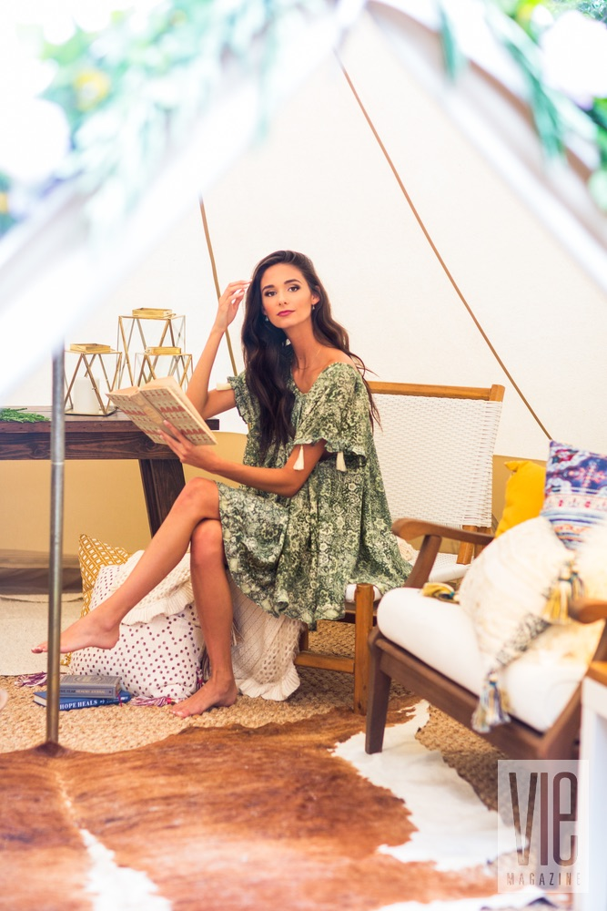Brunette model inside the tent reading a book fancy camping glamping outdoors