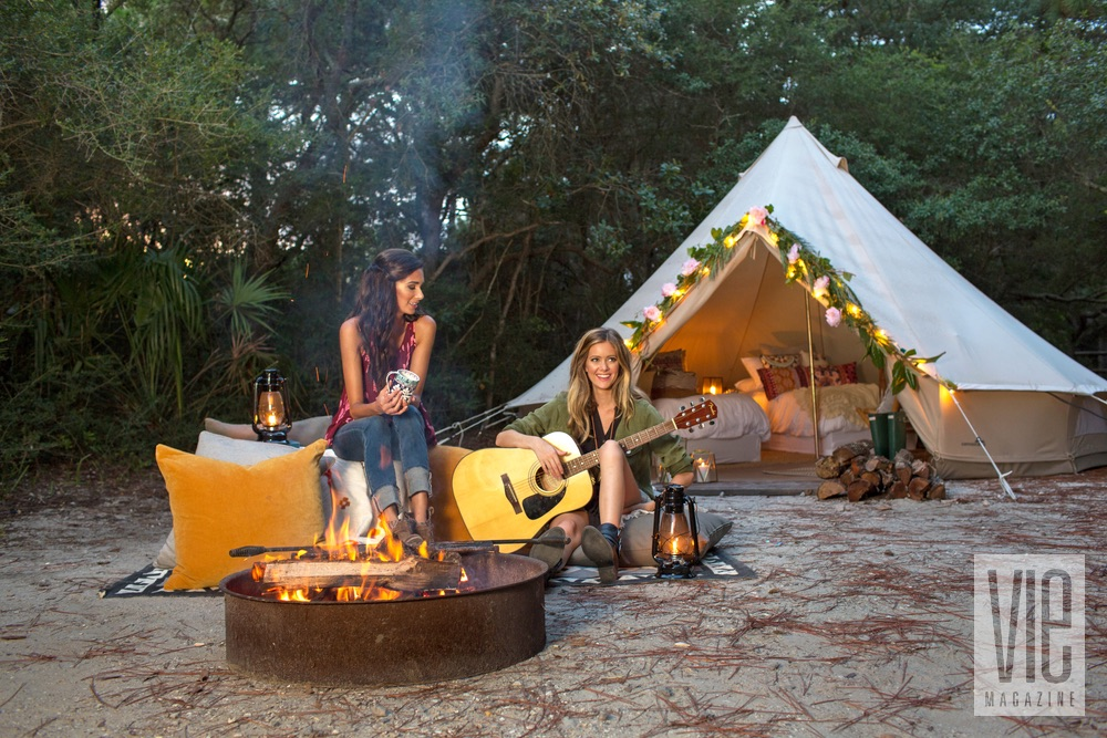Girls drinking coffee and playing guitar by the fire Fancy Camps Glamping