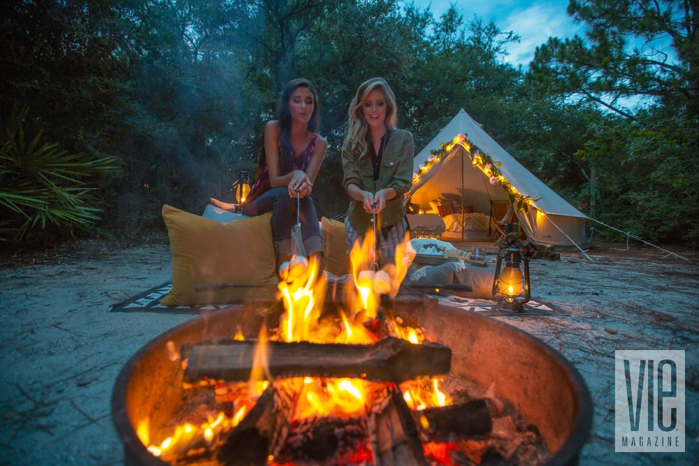Girls making s'mores by the campfire Glamping Fancy Camps VIE Magazine