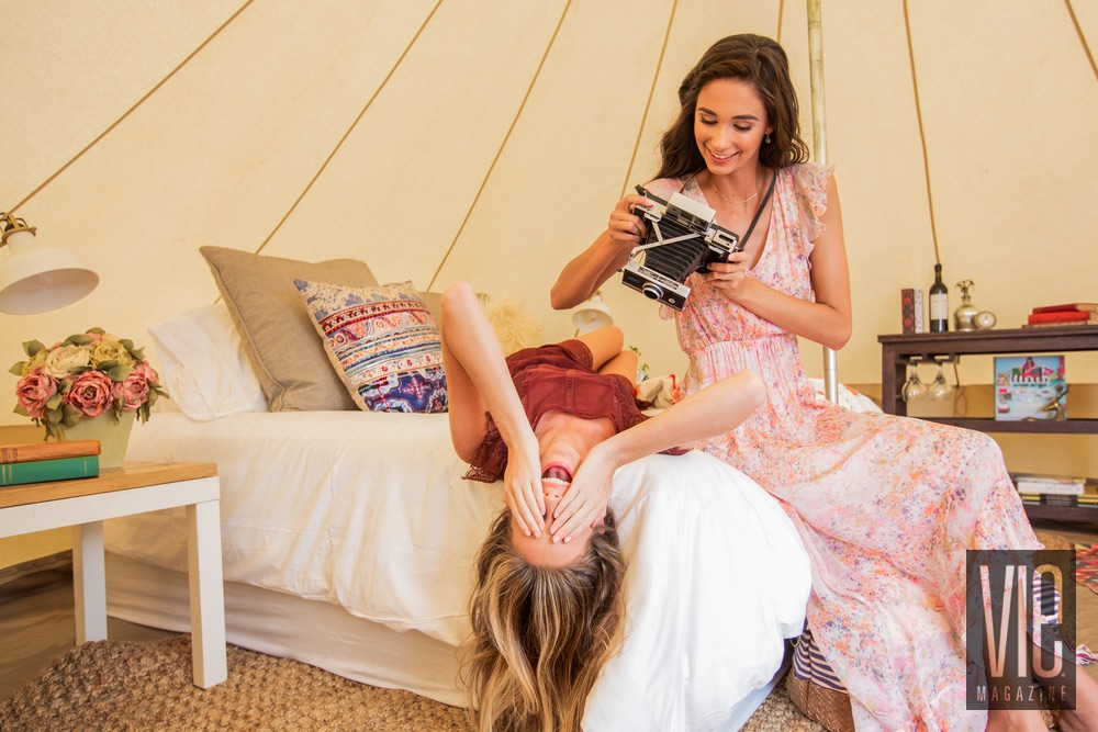Models playing with a camera inside a Fancy Camps tent Glamping VIE Magazine
