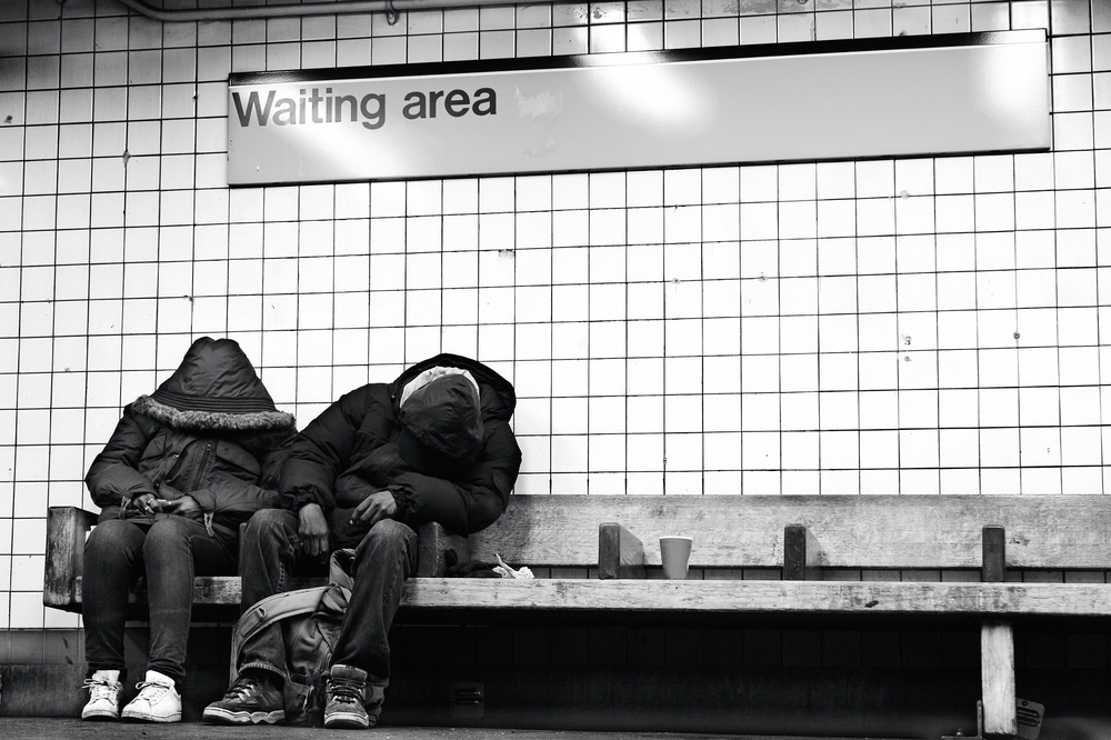 Homeless couple sitting on subway bench sleeping